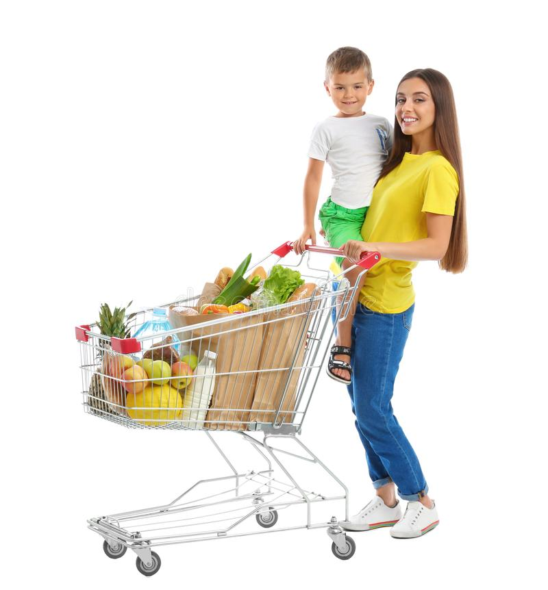 Mother and son with full shopping cart on background. Mother and son with full shopping cart on white background royalty free stock images