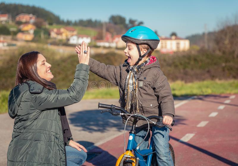 Mother and son giving five by success riding bicycle royalty free stock photography