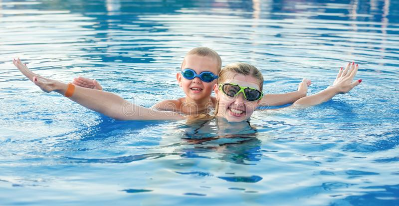 Mother and son in glasses for swimming swim in the pool.Family vacation. stock photo