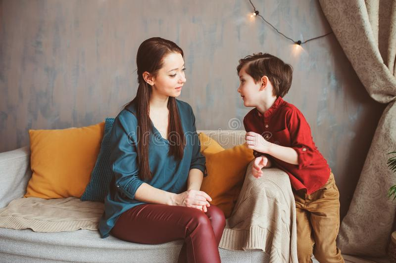 Mother and son happy together at home, sitting at cozy couch. stock images