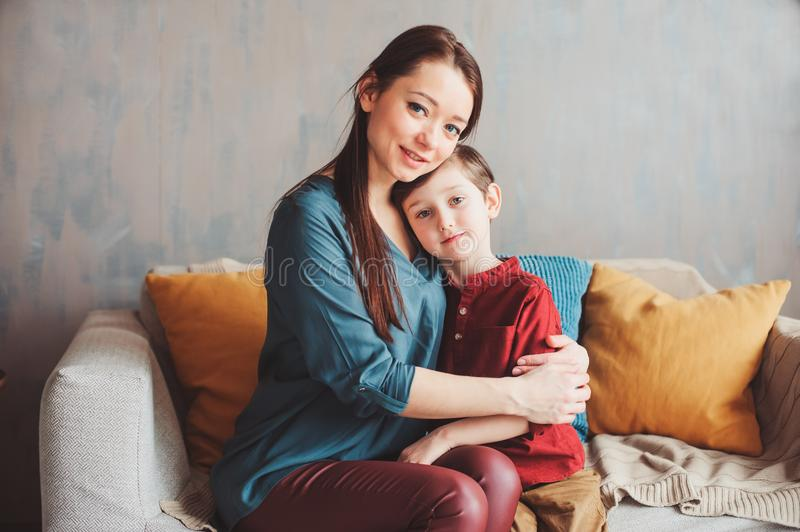 Mother and son happy together at home, sitting at cozy couch. Moving to new home concept, casual family modern life royalty free stock photography