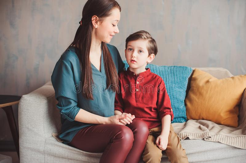 mother and son happy together at home, sitting at cozy couch. stock image
