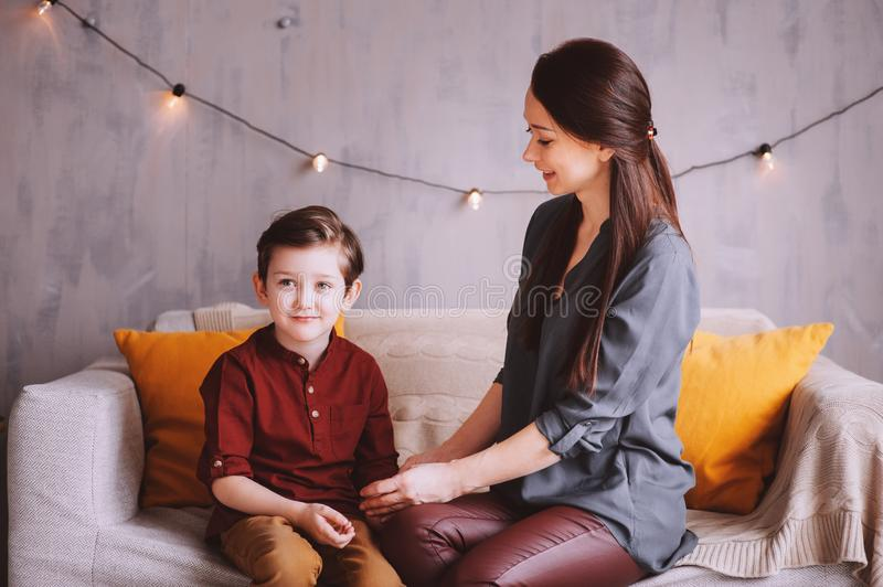 Mother and son happy together at home, sitting at cozy couch. stock photography