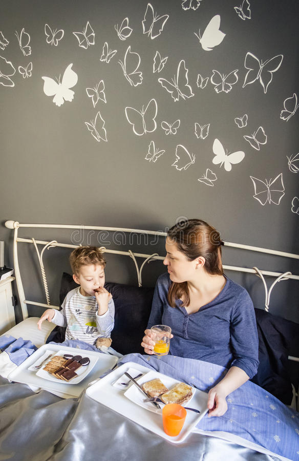 Mother and son having breakfast in bed stock image