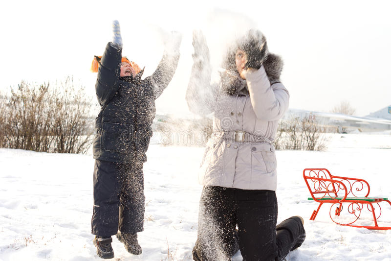 Mother and son having fun in the snow royalty free stock image