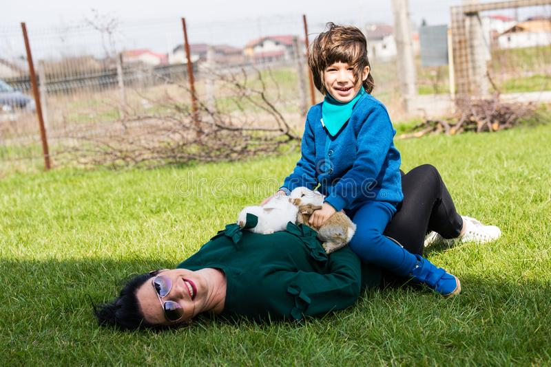Mother and son having fun together. In the garden with little rabbits stock photos