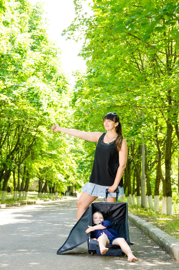 Mother and son hitchhiking. Quiet country road with little boy curled up inside open suitcase as they wait for lift stock image