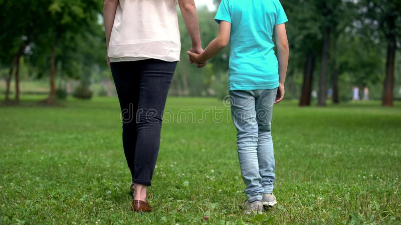 Mother and son holding hands, walking away together, concept of child adoption stock photography