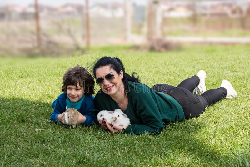 Mother and son holding small rabbits. And sitting together on grass royalty free stock photography