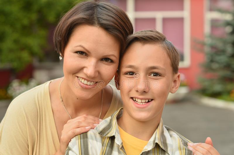 Mother and son hugging outdoors stock image