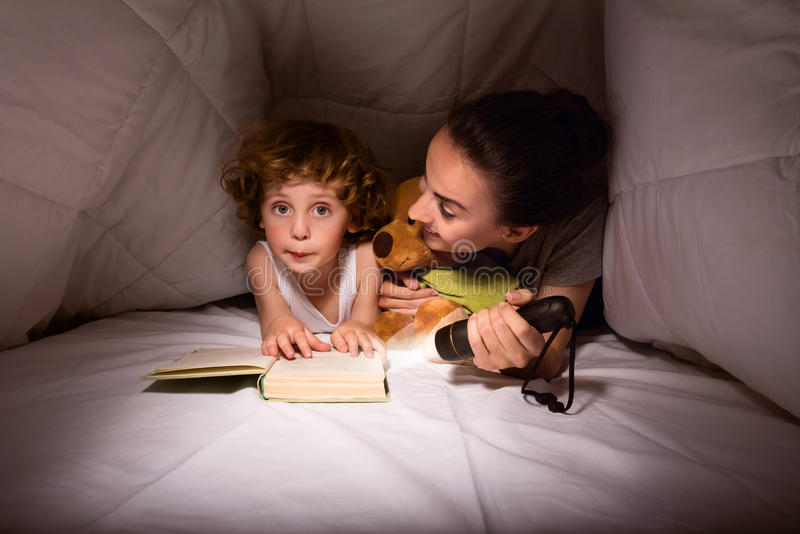 Mother and son in a hut of blankets. Our secret place. Cute little boy reading a story with his mother and using a flashlight in their hut of blankets royalty free stock photo