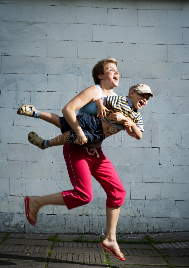 Mother and son jumping. Mother and son jumping against the wall royalty free stock images