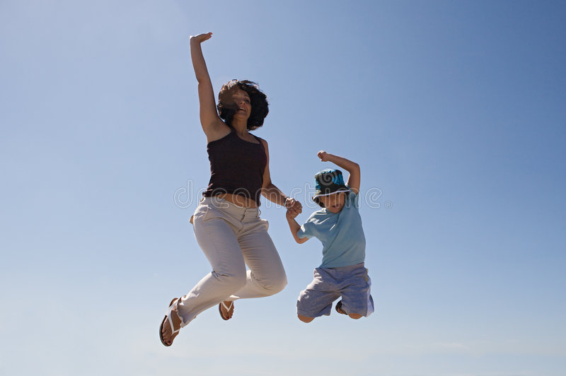 Mother and son jumping. A over sky background royalty free stock image