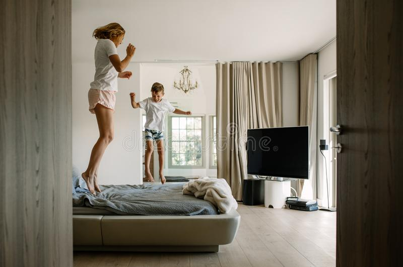 Mother and son jumping on bed royalty free stock images