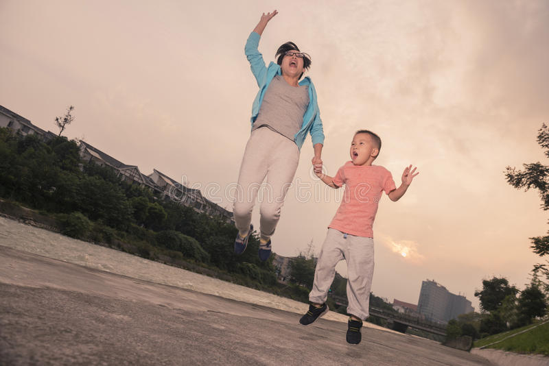 Mother son jumping. Chinese happy mother son jumping up at nightfall royalty free stock photography