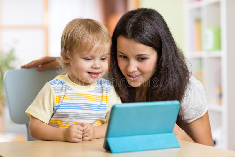 Mother and son kid playing with tablet computer. Young women and her son kid playing with tablet computer indoors stock photos