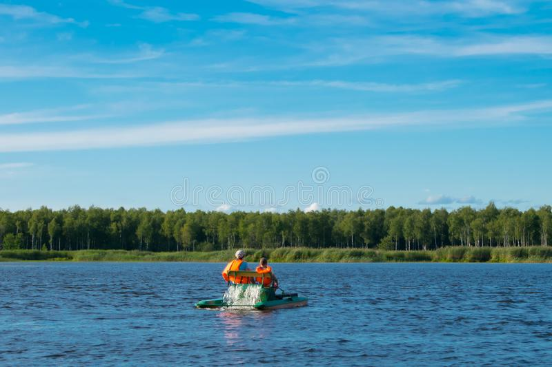 Mother and son in life jackets, riding a catamaran in the open water, beautiful landscape stock photography
