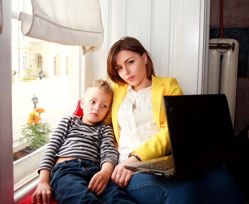 Mother and son looking at laptop at home in room royalty free stock images