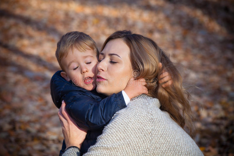 Mother and son love. I love you mom, young mother with her little son in hug, autumn day in park, closeup stock photo