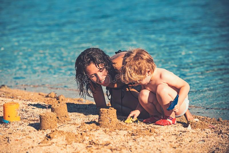 Mother with son make sand castle at sea. Happy family on Caribbean sea. Summer vacation and travel to ocean. Maldives or stock image
