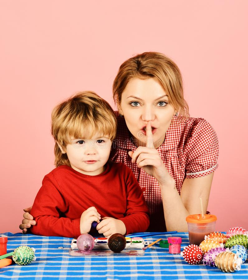 Mother and son making Easter decorations. Woman and child with happy faces on pink background. Mom and boy spend time royalty free stock photography
