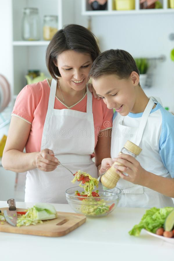 Close up portrait of mother and son making fresh salad at kitchen stock photography