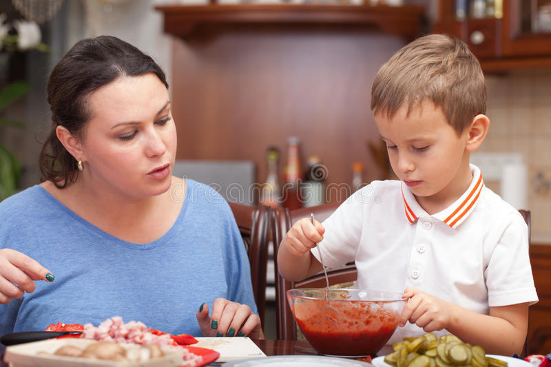 Mother and son making pizza together. At home stock image