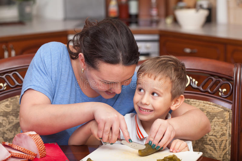 Mother and son making pizza together. At home stock photos