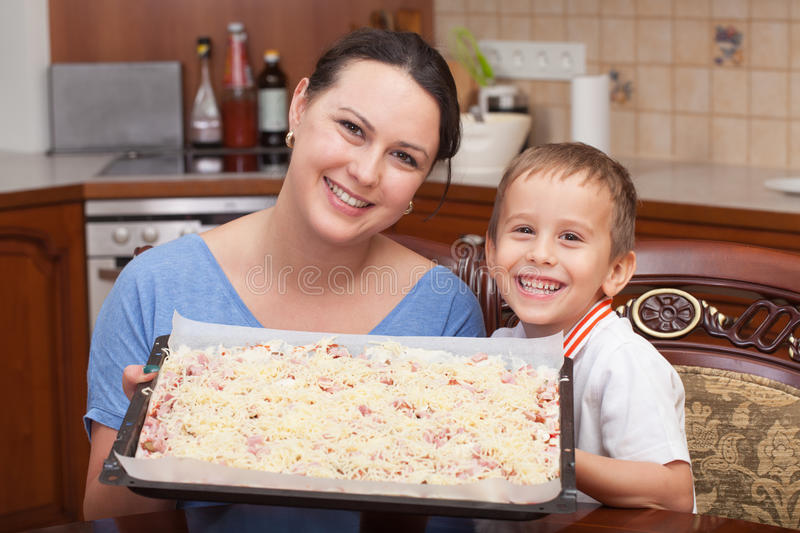 Mother and son making pizza together. At home stock photography
