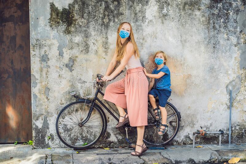 Mother and son in medical mask on a bicycle. Public street art Name Children on a bicycle painted 3D on the wall that`s. Two little Chinese girls riding bicycle royalty free stock photography