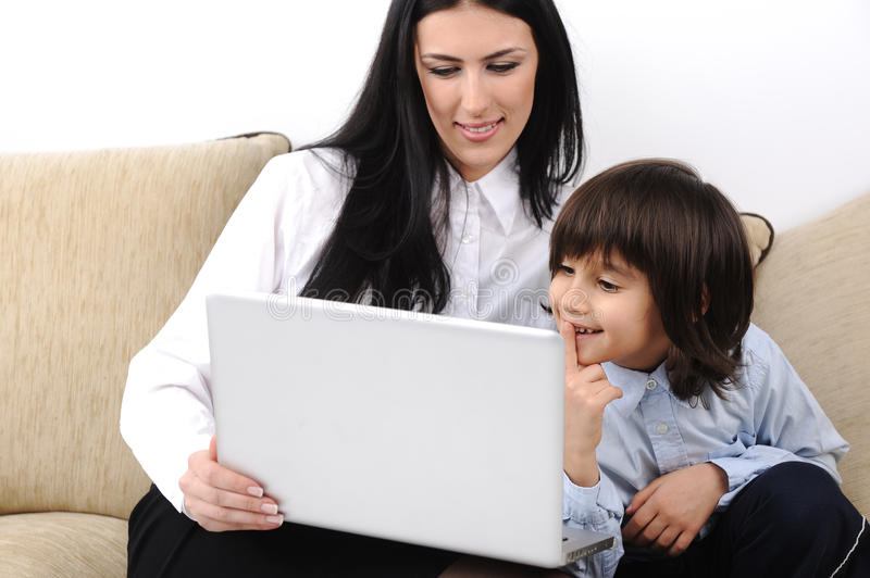 Mother and son with notebook. On couch together royalty free stock image