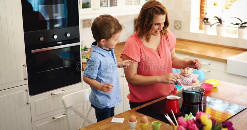 Mother and son paint Easter eggs royalty free stock photography