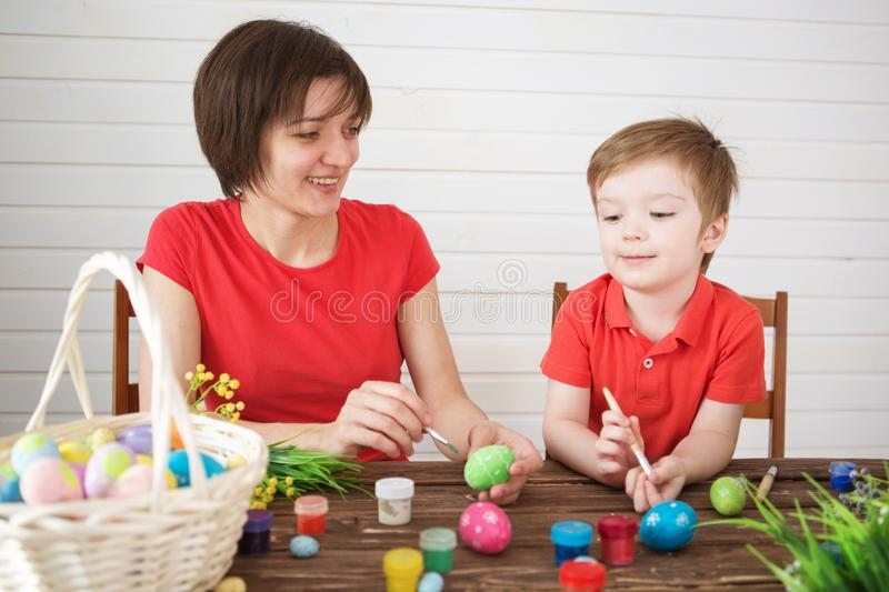 Mother and son painting Easter eggs. Happy family Mom and children son paint easter eggs with colors. Preparation for holiday stock image