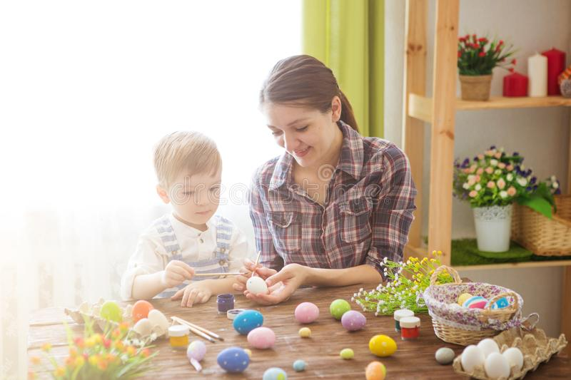 Mother and son painting Easter eggs. Happy family Mom and children son paint easter eggs with colors. Preparation for holiday stock photos