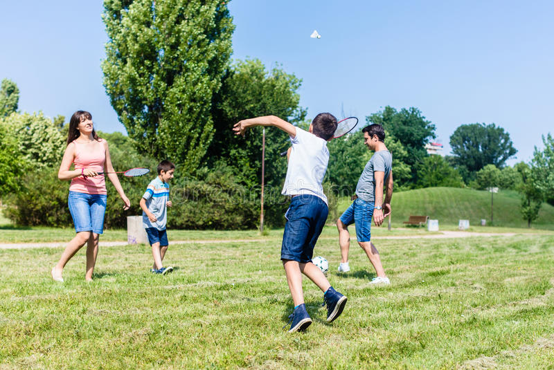 Mother and son playing badminton in park in summer stock photo