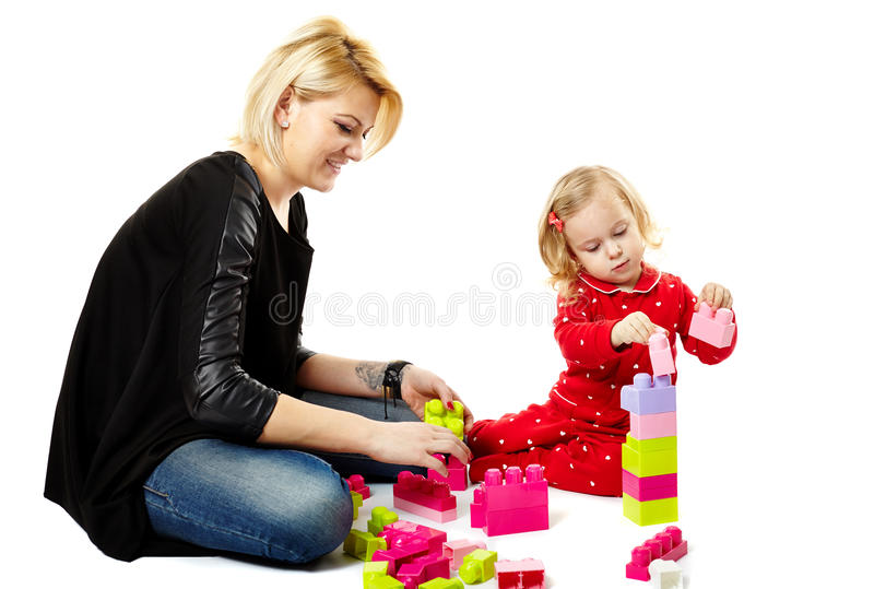 Mother and son playing with colorful cubes. Studio shot of mother and son playing with colorful cubes, sitting on the floor isolated over white background stock photo