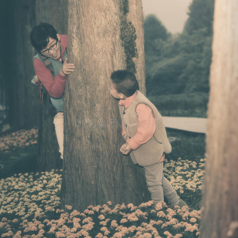Mother son playing hide seek games. Chinese mother son playing hide seek games in forest stock photos