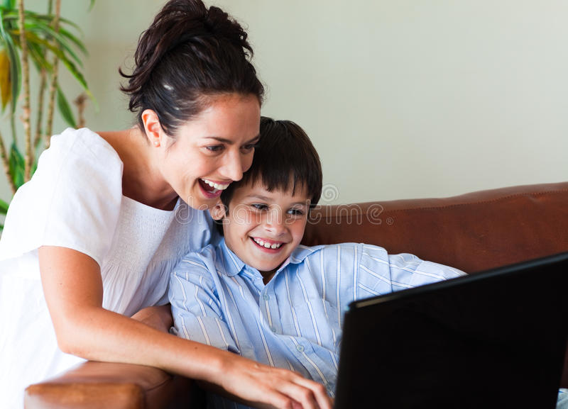 Mother and son playing with a laptop stock image