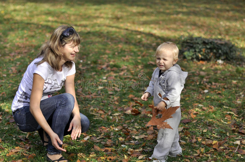 Mother and son playing in the park in the autumn