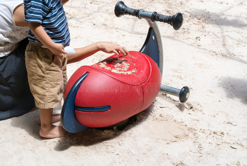 Mother and son playing with sand on colorful equipment in playground royalty free stock image