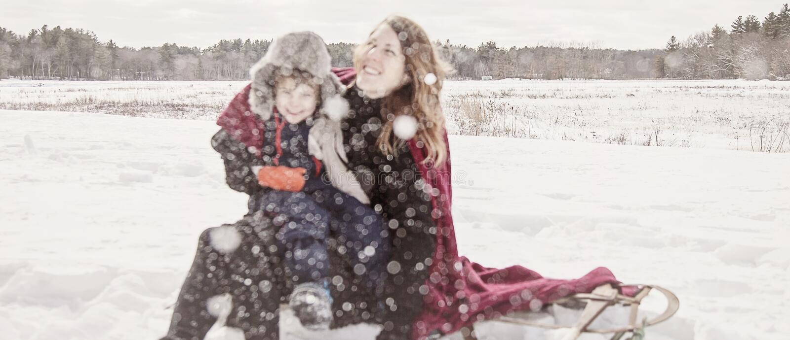 Mother and son playing in snow. Snowflake bokeh blur of Mother and son outside in winter throwing /playing in snow royalty free stock images