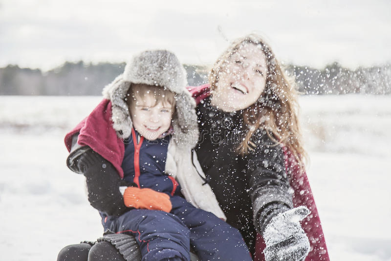 Mother and son playing in snow. Snowflake bokeh blur of Mother and son outside in winter throwing /playing in snow royalty free stock image