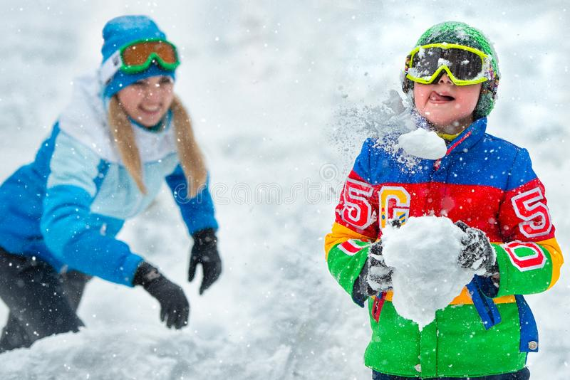 Mother and son playing snowballs on a frosty winter day. Winter holidays.Family winter fun for Christmas vacation. royalty free stock photography