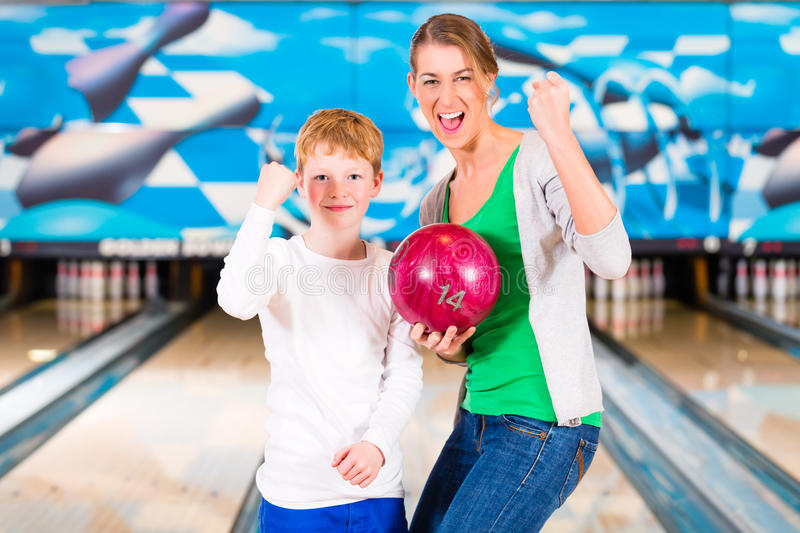 Mother and son playing together at bowling. Center royalty free stock photos