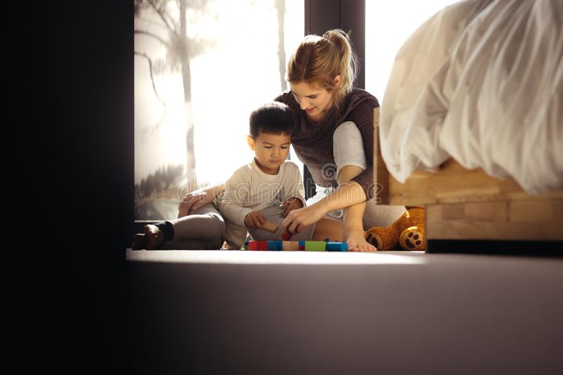 Mother and son playing with toys in bedroom royalty free stock photos