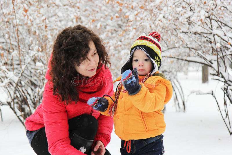Mother and son playing in winter park stock photo