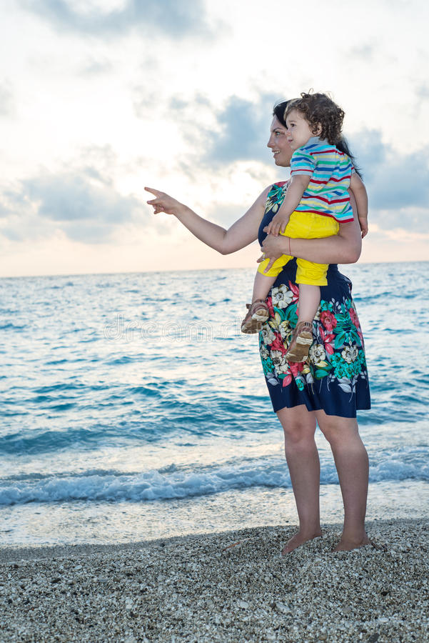 Mother with son pointing on beach royalty free stock images