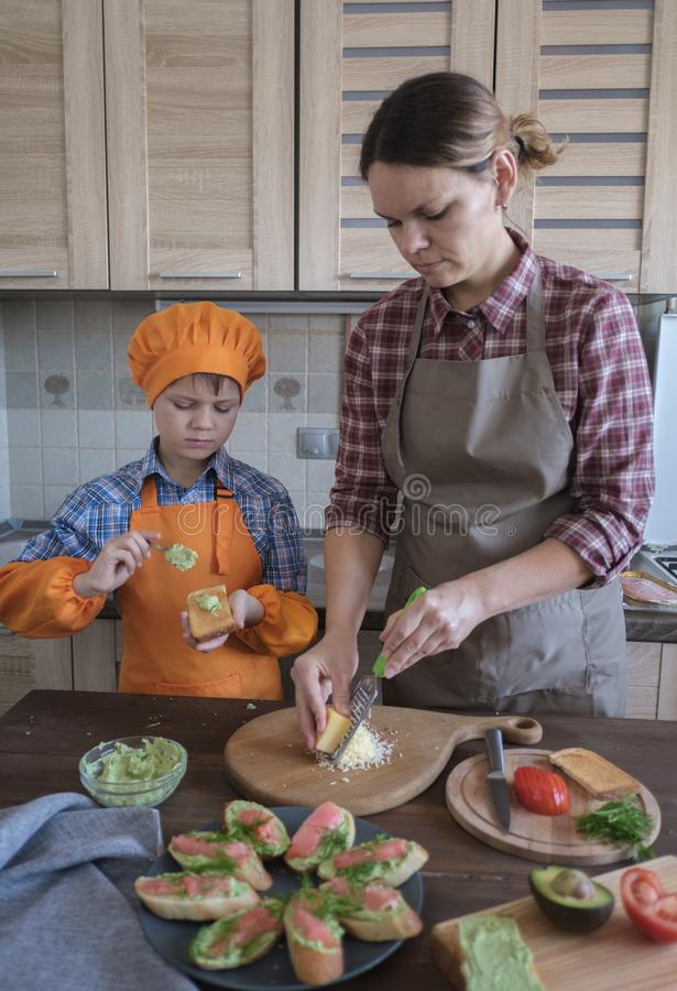 Mother and son prepare delicious sandwiches with avocado , salmon, cheese and tomatoes in the kitchen royalty free stock photography
