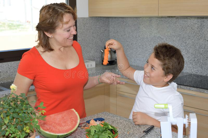 Mother and son preparing lunch and smile. Child jokes with a carved carrot. Mother and son preparing lunch in the kitchen and smiles. Child jokes with a carved royalty free stock photography