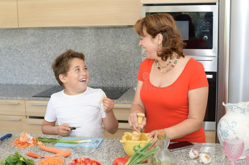 Mother and son preparing lunch and smile. Child jokes with a garlic royalty free stock photos